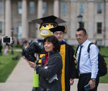 Graduate and family taking photo with Herky