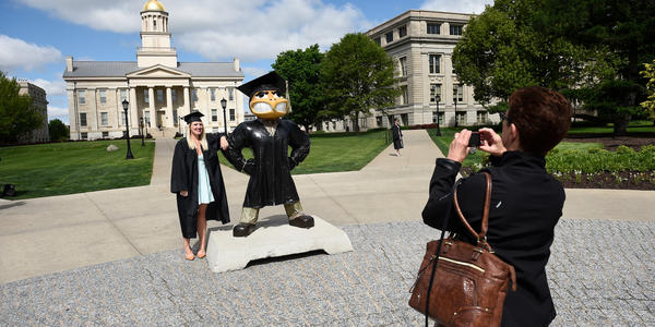 Graduate posing with Herky